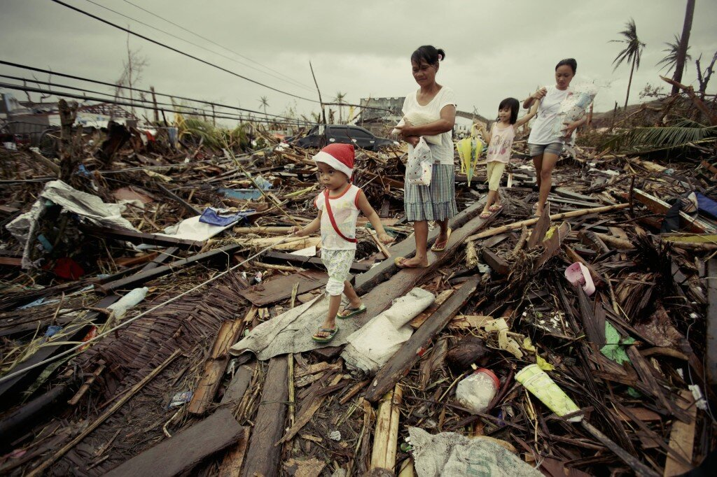 Survivors walk by damages at typhoon ravaged Tacloban city, Leyte province, central Philippines on Tuesday, Nov. 12, 2013. (AP Photo/Aaron Favila)