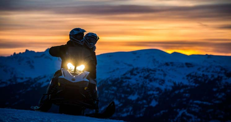 couple riding a snowmobile on blackcomb mountain as the sun sets