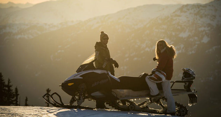 couple watching sunset on whistler snowmobile tour